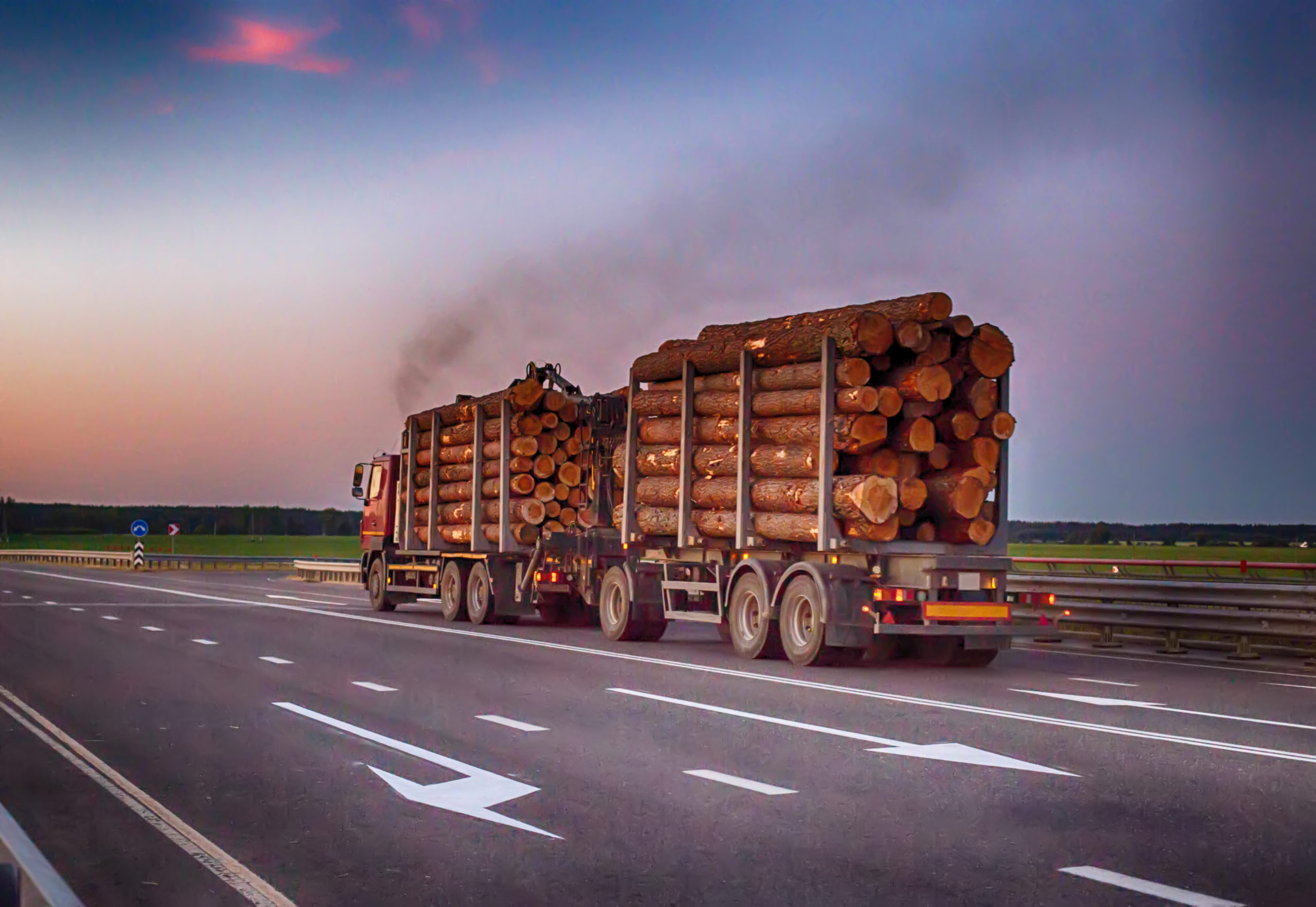 A Loaded Truck Transports Timber Logs With An Overload On The Highway. Overloaded Trucks Injury Lawyer